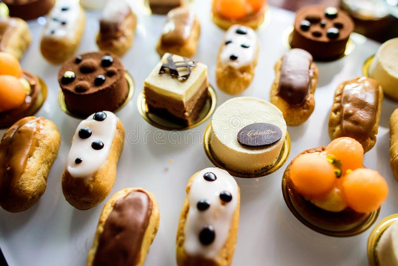Eclairs. Mixed colored delicious sweets. Colored delicious sweets with cream, biscuits and eclairs stock images