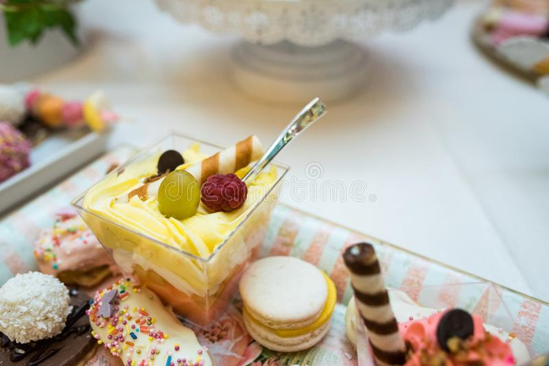 Mixed colored delicious sweets. Colored delicious sweets with cream, biscuits and fruits stock photography