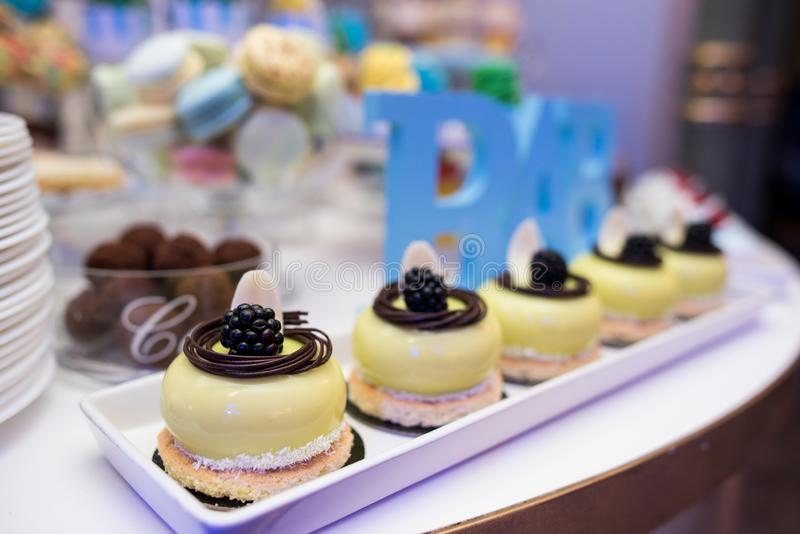 Mixed colored delicious sweets. Colored delicious sweets with cream, biscuits and fruits stock images