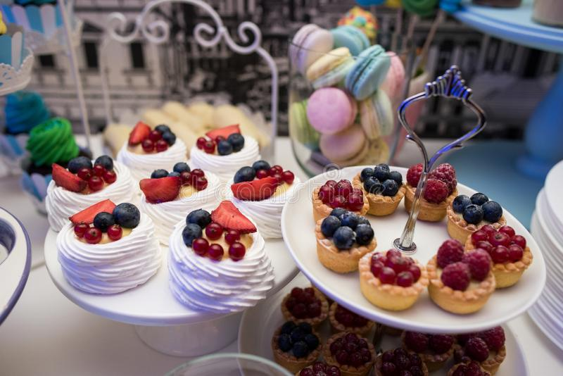 Mixed colored delicious sweets. Colored delicious sweets with cream, biscuits and fruits royalty free stock photo