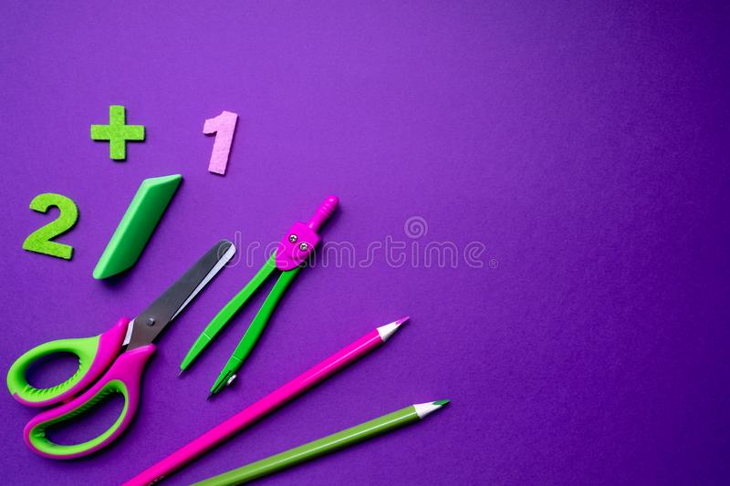 Colored different school supplies on lilac paper background. Back to school concept. Flat lay, copy space royalty free stock photos
