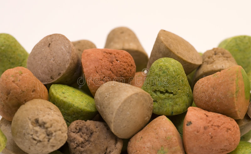 Colored Dog Treats. Red, green and brown dog treats on a white background royalty free stock photos