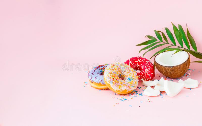 Colored donuts with colorful sprinkles and coconut on pink background. Colorful breakfast concept. Copy space. Close-up stock photos