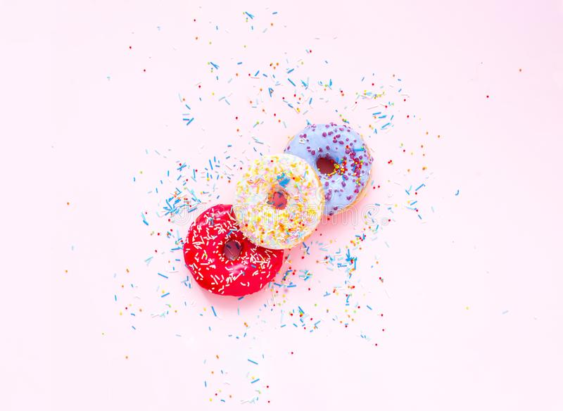 Colored donuts with colorful sprinkles on pink background. Concept colorful breakfast. Copy space. Close up royalty free stock photo