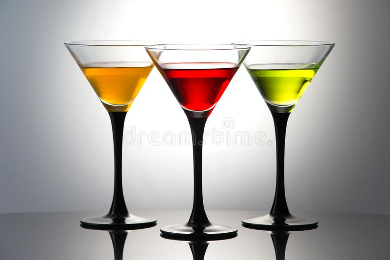 Coloured drinks in martini glasses, cocktails with liqueurs stock image