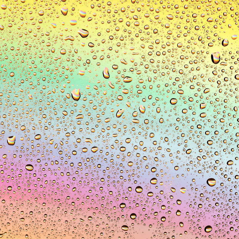 Colored drops on a rainbow background royalty free stock image