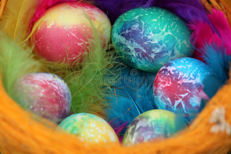Colored easter eggs in basket royalty free stock photos