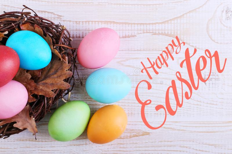 Colored Easter eggs in a nest, on a white wooden table. Text, happy easter stock image