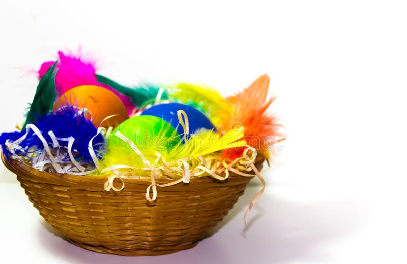 Easter basket with eggs and colorful feathers on white background royalty free stock images