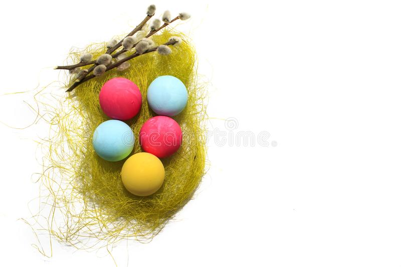 Colored Easter eggs on a white background and a willow twig. Colored Easter eggs red, yellow, blue on a white background and a willow twig royalty free stock photos