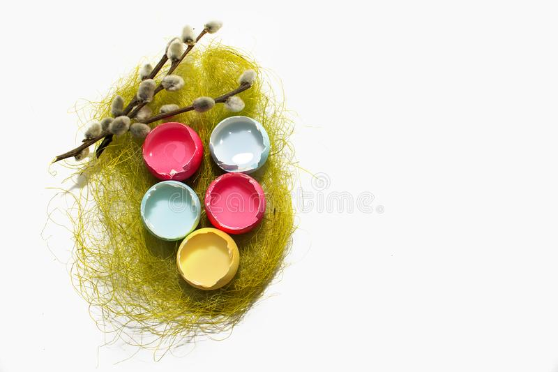 Easter eggs on a white background and a willow twig. Colored Easter eggs red, yellow, blue on a white background and a willow twig stock photo