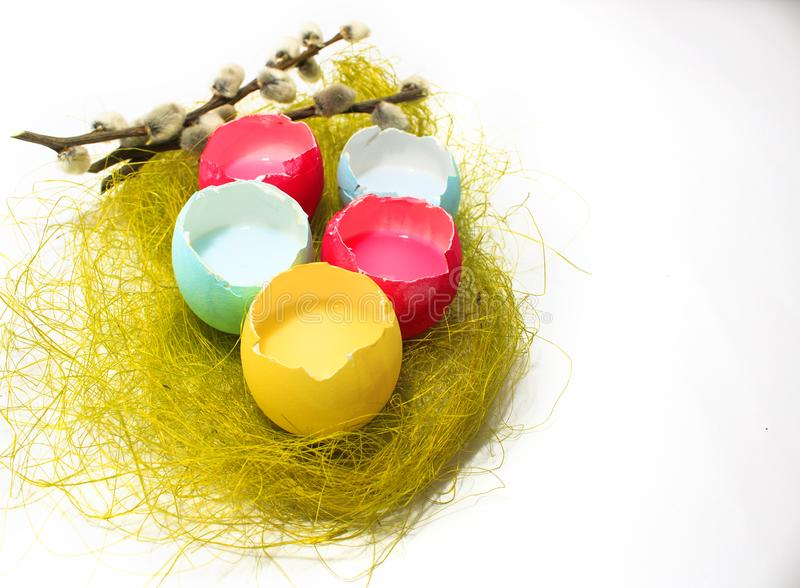 Easter eggs on a white background and a willow twig. Colored Easter eggs red, yellow, blue on a white background and a willow twig stock photos