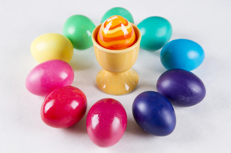 Colored eggs in a cup on a white background royalty free stock photo