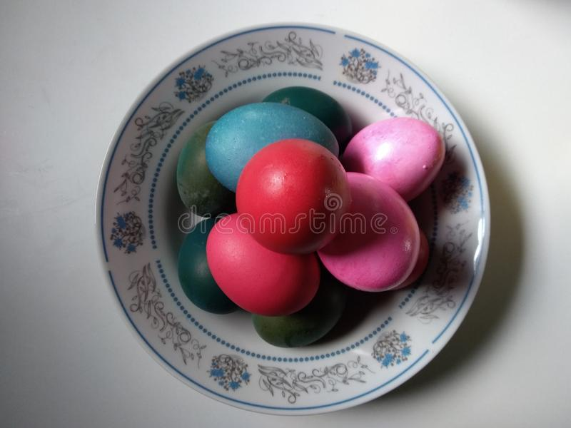 Colored eggs on a plate, easter stock photography