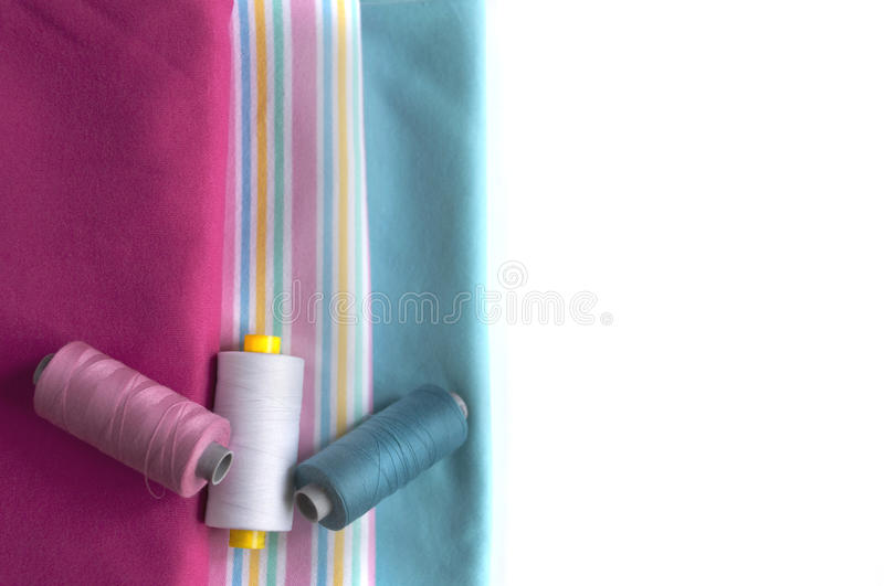 Colored fabrics with appropriate spool of thread. Colored fabrics with suitable in color sewing thread on the white background royalty free stock image