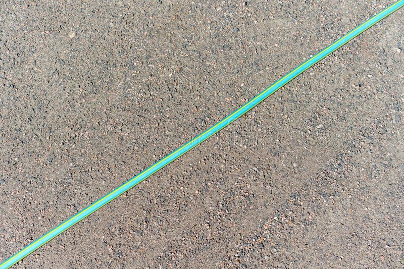 Colored garden hose for watering diagonally across the garden path royalty free stock images