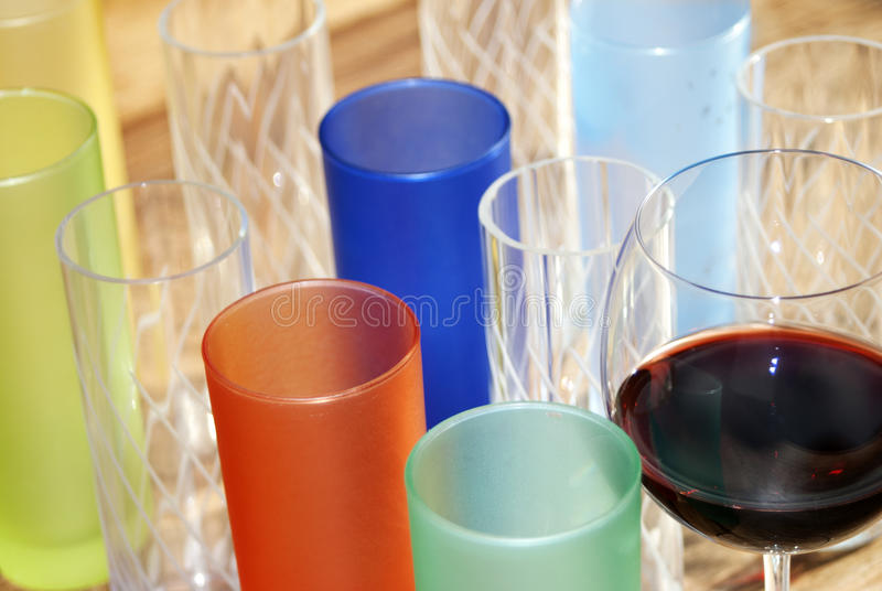 Colored glasses. Colored cocktail glasses on a table for a plays of light and colors stock photo