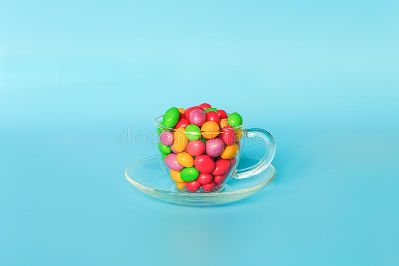 Colored glazed candy beans. Glass mug on saucer filled with colorful button-shaped chocolates on blue background with copy space. Concept sweet tea party royalty free stock image