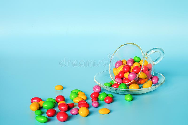 Colored glazed candy beans. Glass mug on saucer and scattered colorful button-shaped chocolates on blue background with copy space. Concept sweet tea party stock images