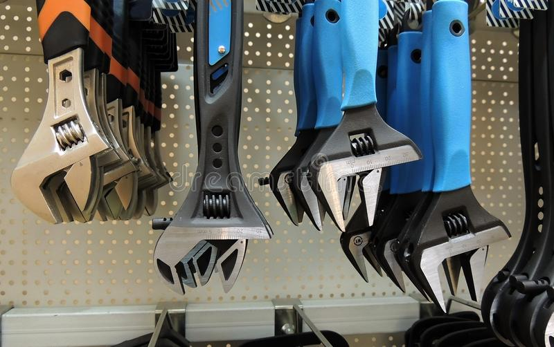Colored grip wrenches on the shelf at hardware shop. Soft grip spanners hanging on the tools rack royalty free stock photo