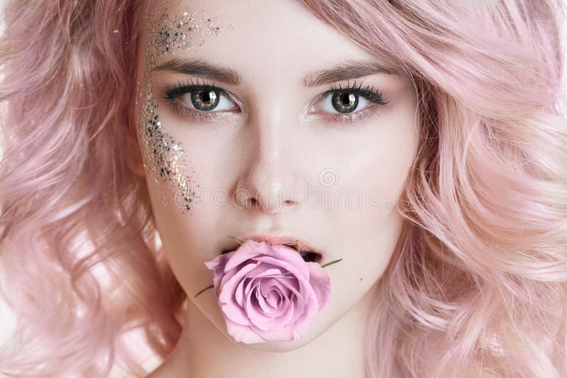 Colored hair. Beauty women portrait of young curly woman with pink hair, perfect art make-up with glitter. Rose in her royalty free stock photos