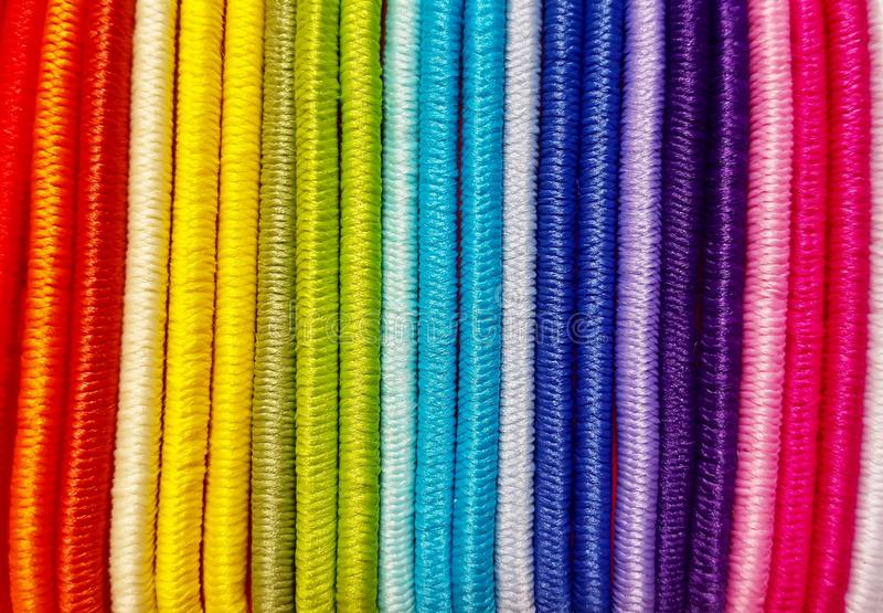 Colored hair ties close together. A vibrant display of brightly colored hair ties all in a row and banded close together making a very colorful background stock photo