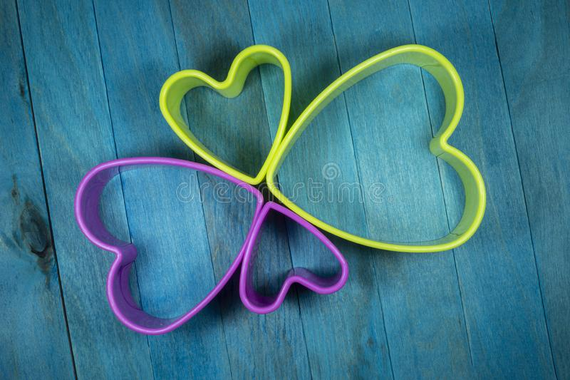Heart-shaped figures on blue background stock images