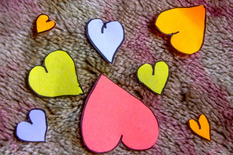 Colorful shaped cut outs wallpaper. Colored heart shaped cut outs wallpaper for design use with messages or on device royalty free stock photo