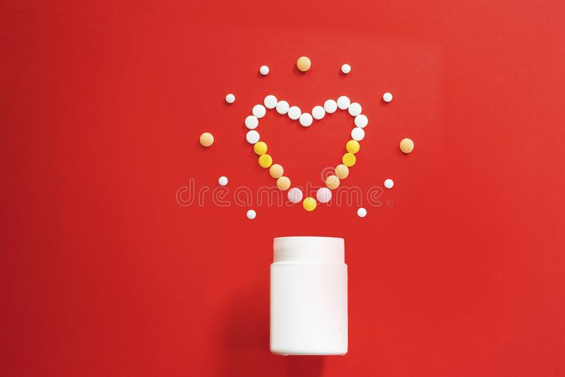 Colored heart from tablets and pills on a red background and box stock photography