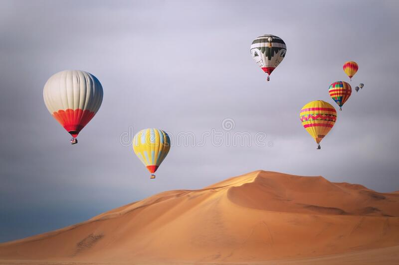 Colored hot air balloons flying over the sand dunes at sunset. Africa royalty free stock image