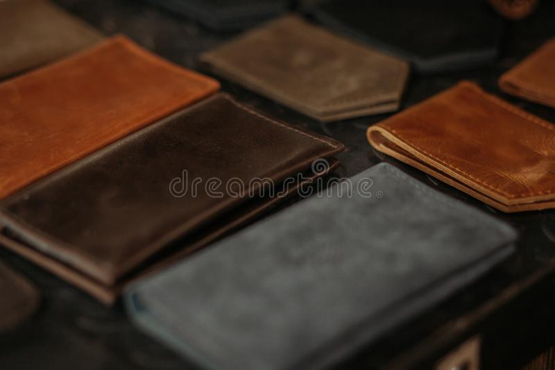 Colored leather passport covers and wallets on the table. Black background. Handmade concept. stock images