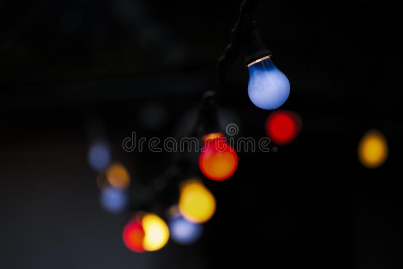 Colored light bulbs on black stock images