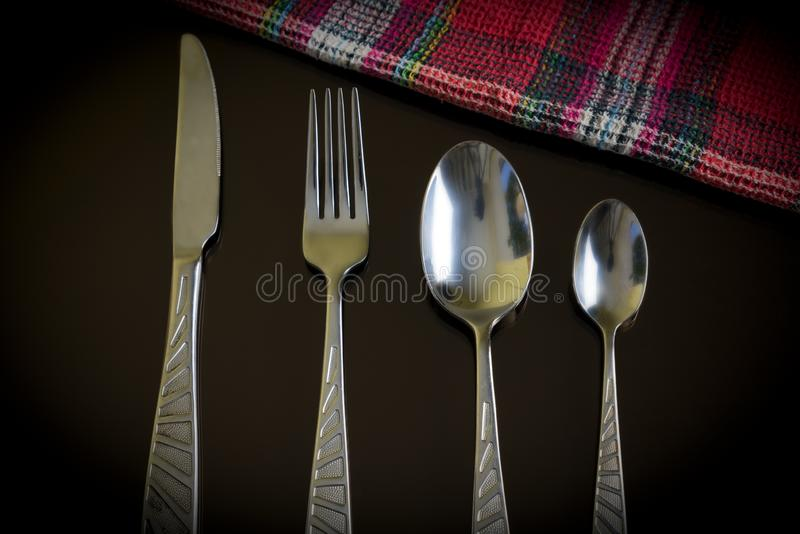 Colored lines table-napkin and cutlery as a still life on dark reflective surface. Silver knife, fork, spoon, teaspoon on the dark reflective backdrop stock photos
