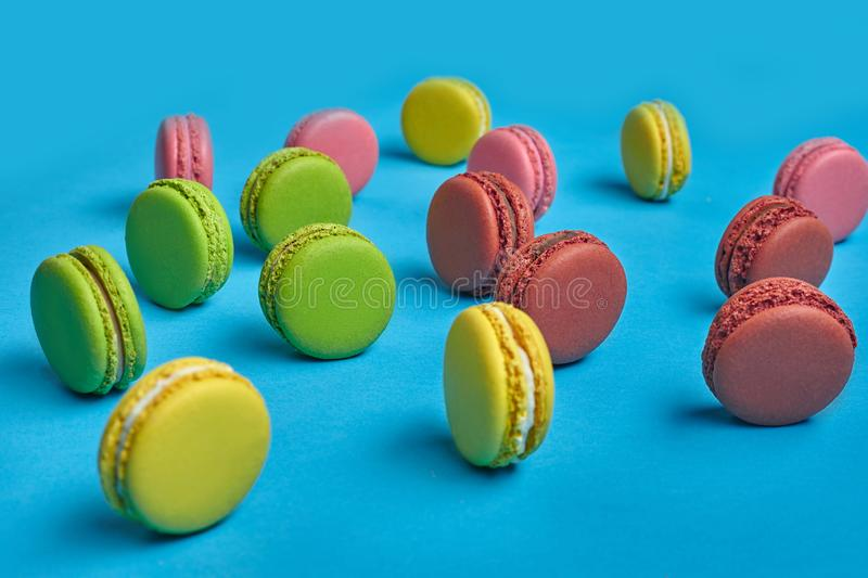 Colored macaron or macaroon, sweet meringue-based confection on blue background. Close-up, copy space. Side view of a delectable macarons or macaroons, sweet stock images