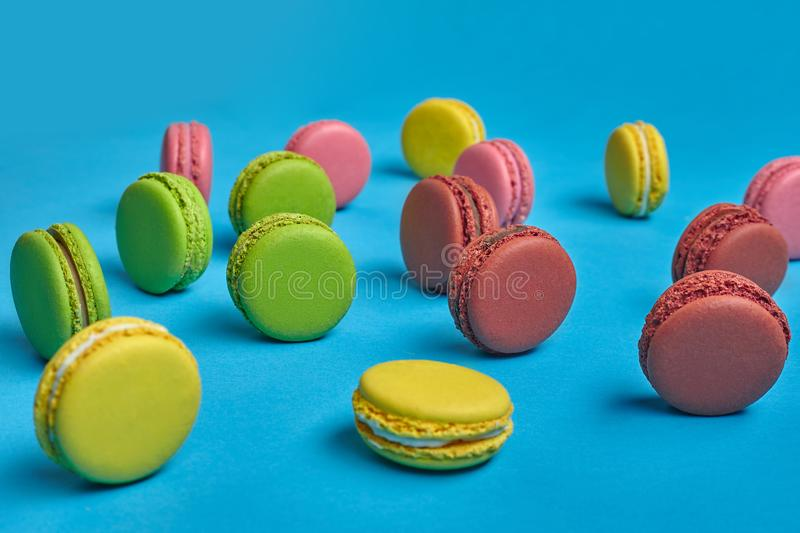 Colored macaron or macaroon, sweet meringue-based confection on blue background. Close-up, copy space. Side view of a delectable macarons or macaroons, sweet stock image