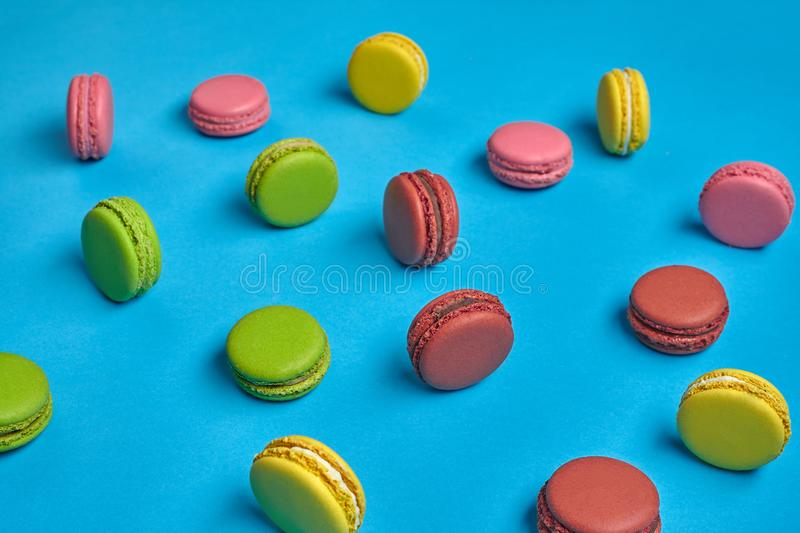 Colored macaron or macaroon, sweet meringue-based confection on blue background. Close-up, copy space. Top view of a nice macarons or macaroons, sweet meringue stock photos