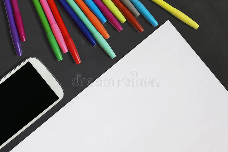 Colored Markers, Blank White Paper, Cell Phone on Black Chalk Board Background, Top View with Copy Space stock photos