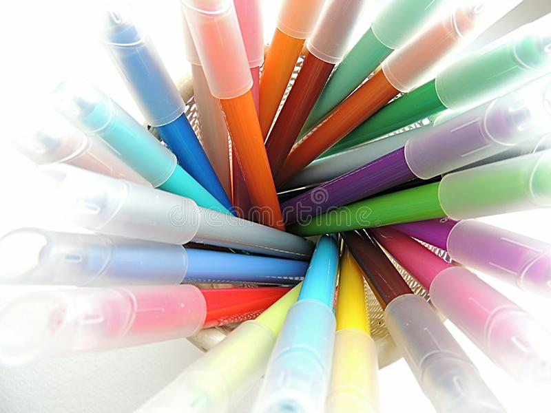 Colored markers in a cup on a white background. Colored markers in a cream cup on a white background stock photography
