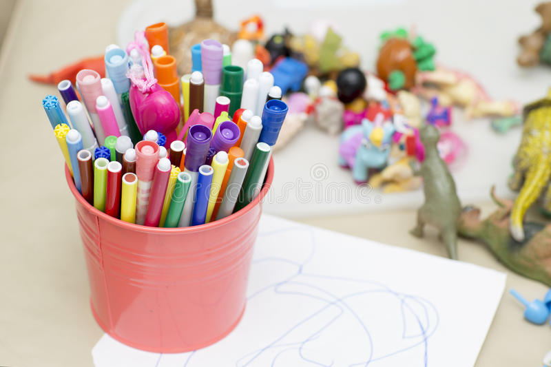 Colored markers are in the pink bucket. stock image