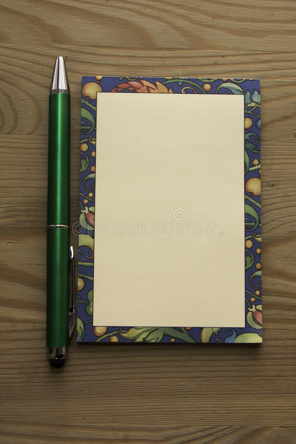 Colored notepad and a green pen on a wooden background. It may be used for writing custom text royalty free stock photos