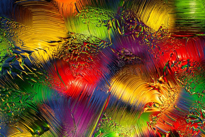 Multi-colored objects depicted through the glass with smears of greasy ointment. Colored objects with side lighting and blurred with glass and transparent stock photography