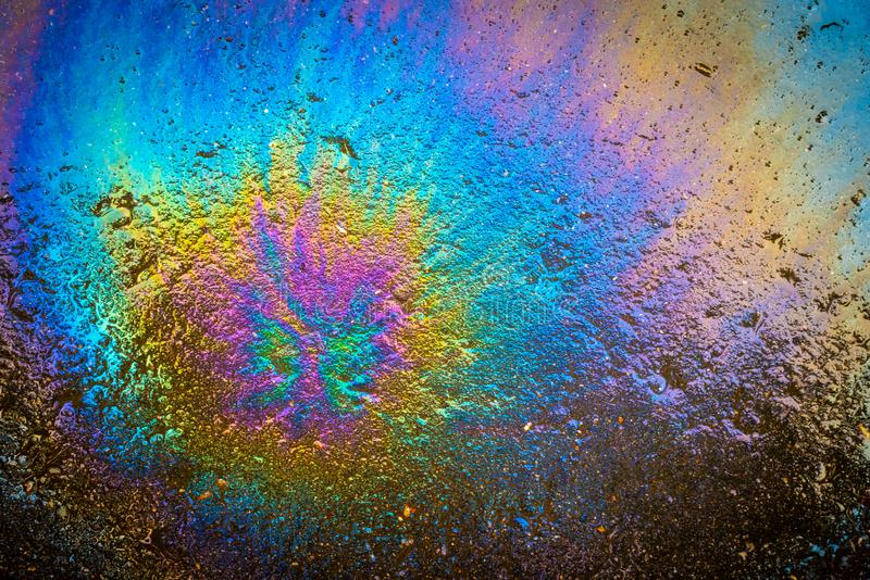 Colored oil stain on the asphalt. A rainbow slick of gasoline. Abstract background royalty free stock photo