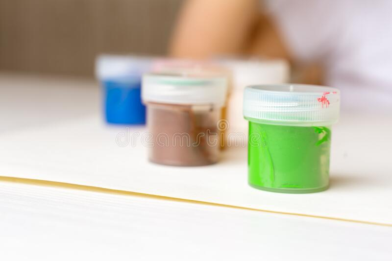 Colored paints stand on the table green, blue, purple and others. Stay home stock photo