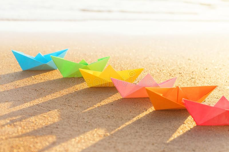 Colored paper boats row on sandy beach outdoors royalty free stock image