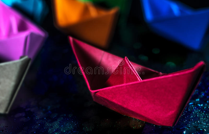 Colored paper boats stock photography