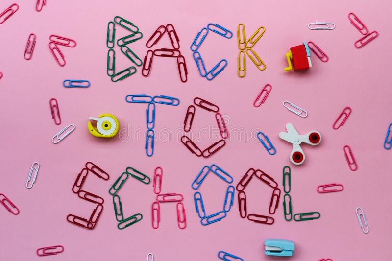 Colored paper clips on a pink background lined with the inscription - back to school. Laid erasers in the form of stationery - scissors, stapler, etc. top view royalty free stock photography