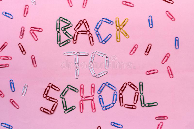 Colored paper clips on a pink background lined with the inscription - back to school. Colored paper clips, stationery. the view from the top, Flatley royalty free stock images