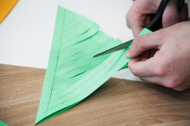 Colored paper is cut with scissors. Scrapbooking and other hobbies stock image