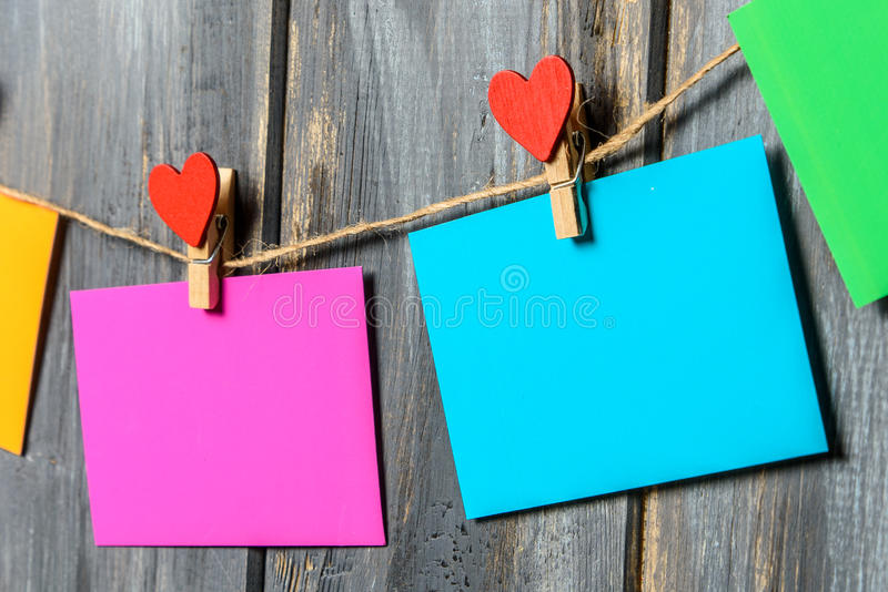 Colored paper sheets on thread with heart shaped clothespin wooden background. Colored paper sheets on thread with heart shaped clothespin on wooden background royalty free stock photography