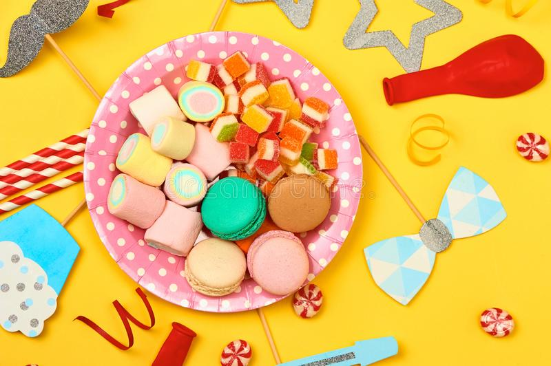 Colored party, sweets and confetti on yellow background top view mockup stock images